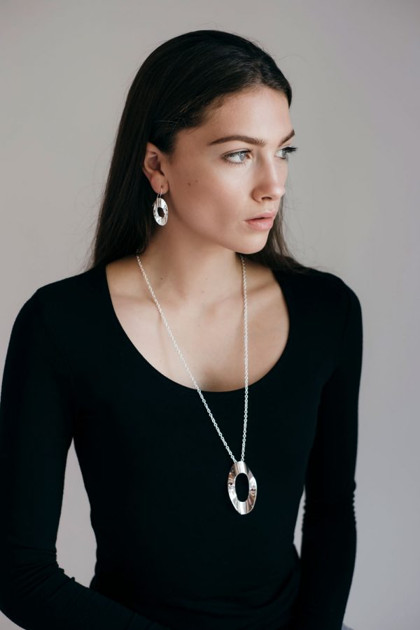 Model wearing the Mirage Medium Earrings and large Mirage Pendant by Black Matter