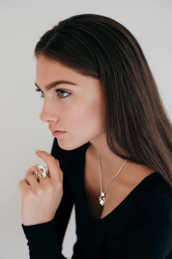 Model wearing the Mirage Flat Ring with the Medium Mirage Pendant by Black Matter