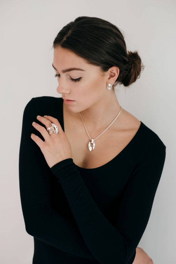 Model wearing the Mirage Stud Earrings with Medium Mirage Pendant and the Low Mirage Ring by Black Matter