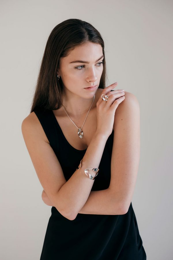 Model wearing the Mirage Stud Earrings with the Medium Pendant, Tall Ring and Mirage Cuff by Black Matter