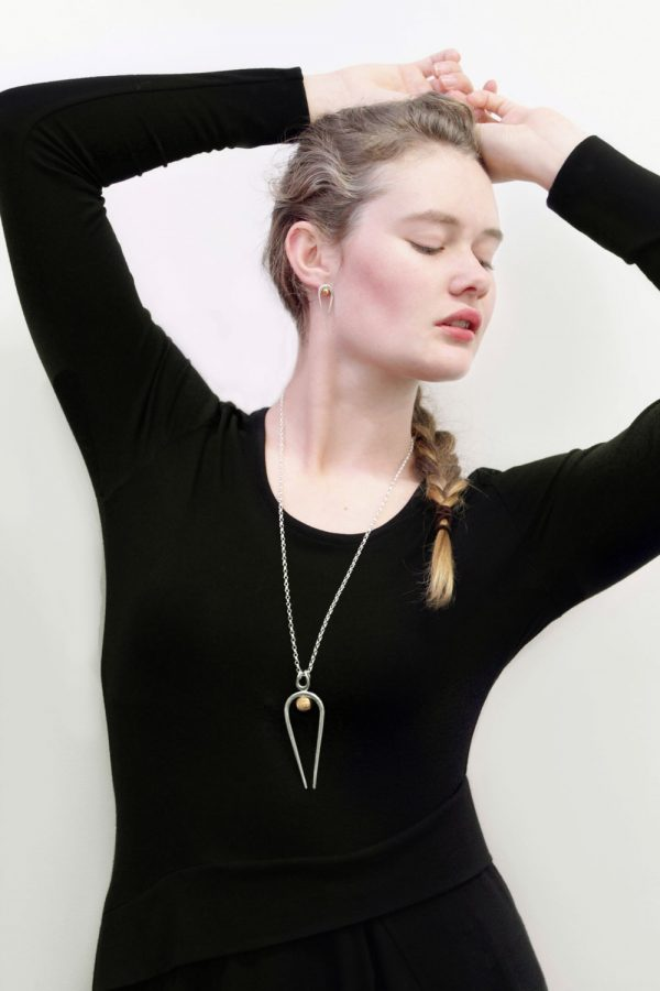 Model wearing the Penumbra Large Pendant and Stud Earrings by Black Matter