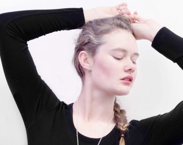 Model wearing the Penumbra Small Stud Earrings by Black Matter