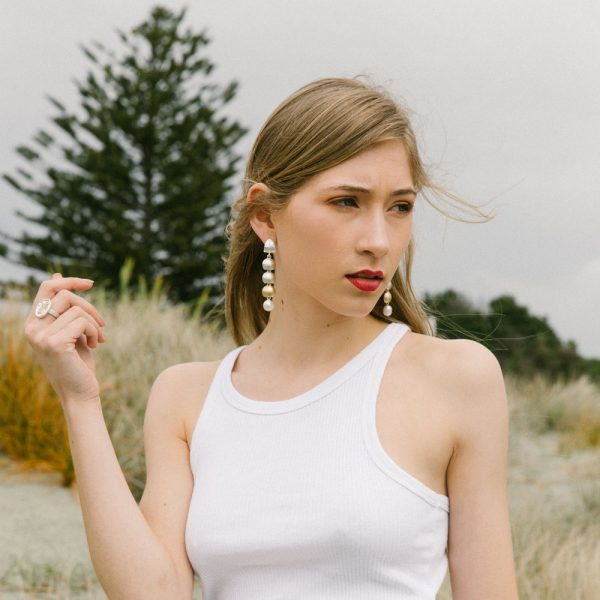 Model wearing the Local Palette Ring and Arctic Drop Earrings by Black Matter