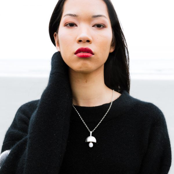 Model wearing the reversible Swing Pendant by Black Matter