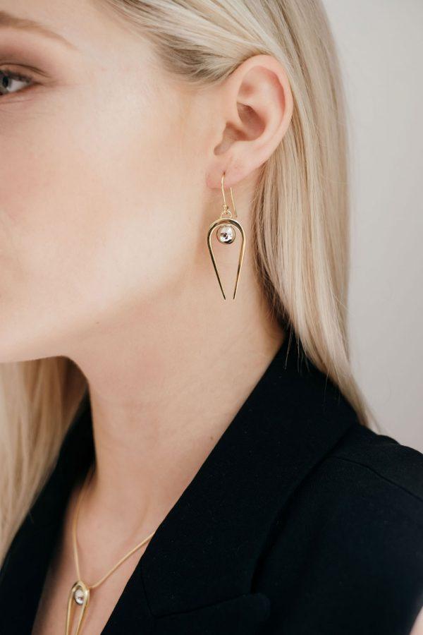Model wearing the Gold Penumbra Medium Earrings by Black Matter