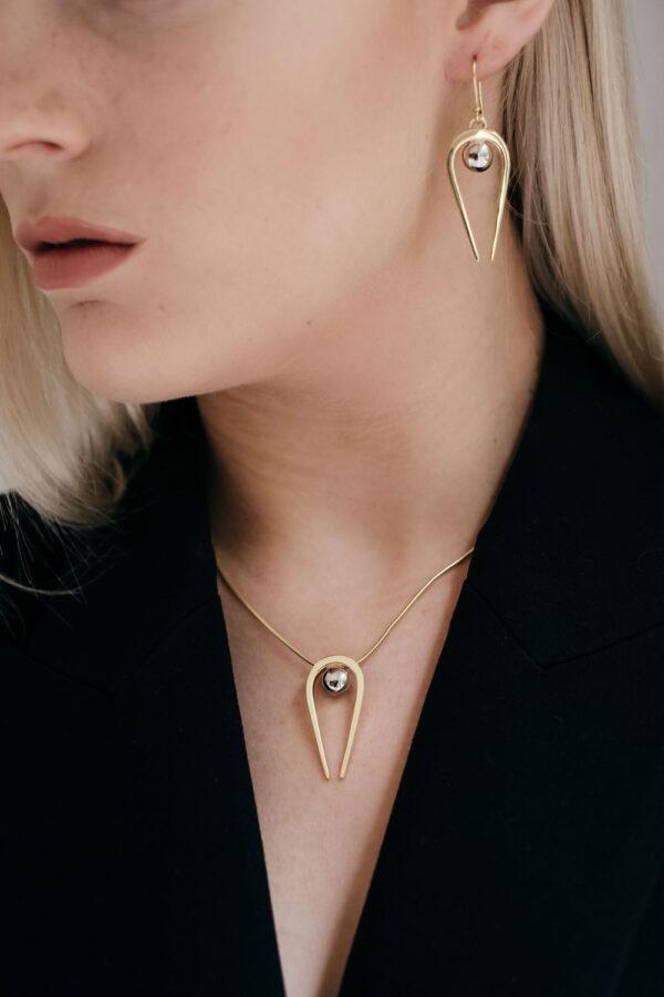 Model wearing the Penumbra Medium Gold Pendant and Earrings by Black Matter