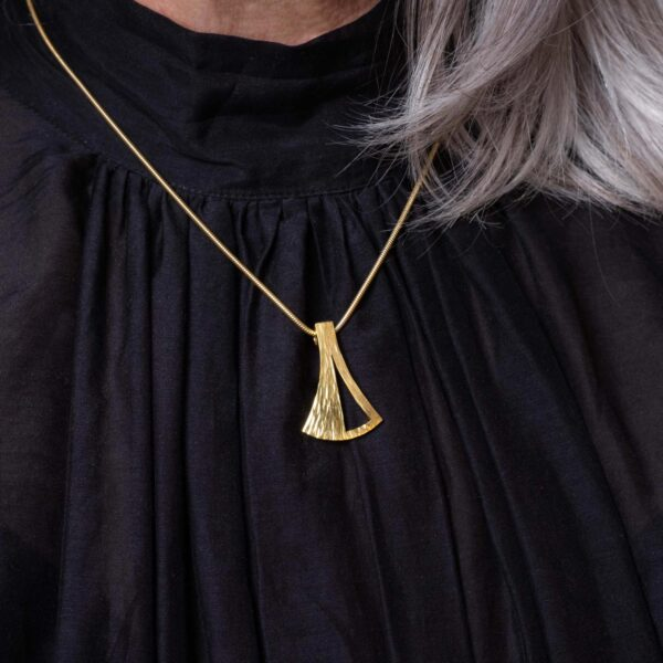 Model wearing the Emergence Medium Gold Pendant by Black Matter