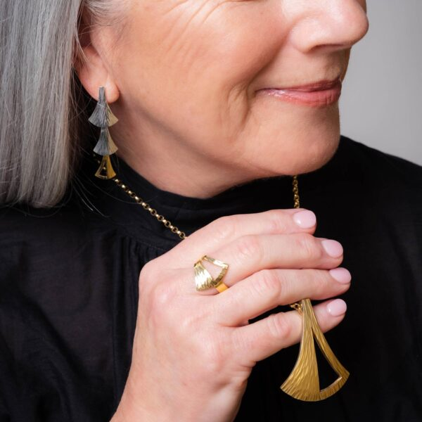 Model wearing the Emergence Large Gold Pendant with the Dual Tone Cascade Earrings and Gold Ring by Black Matter