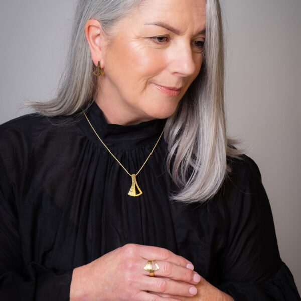 Model wearing the Emergence Medium Gold Pendant with the Gold Stud Earrings and Gold Ring by Black Matter