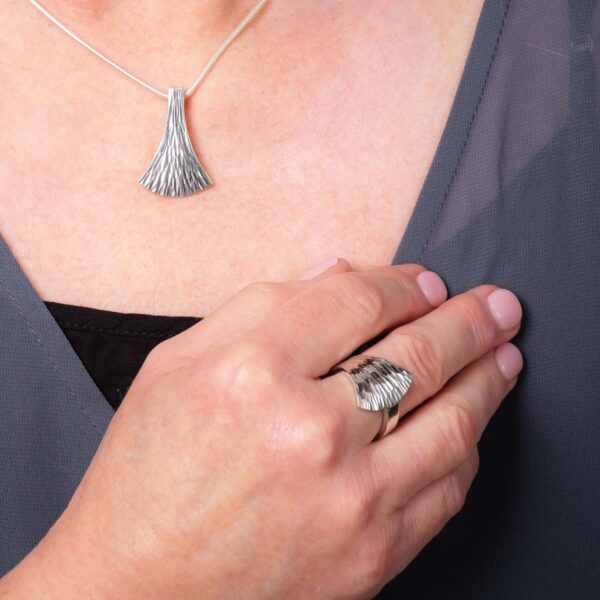 Model wearing the Emergence Silver Ring with the Medium Silver Pendant by Black Matter