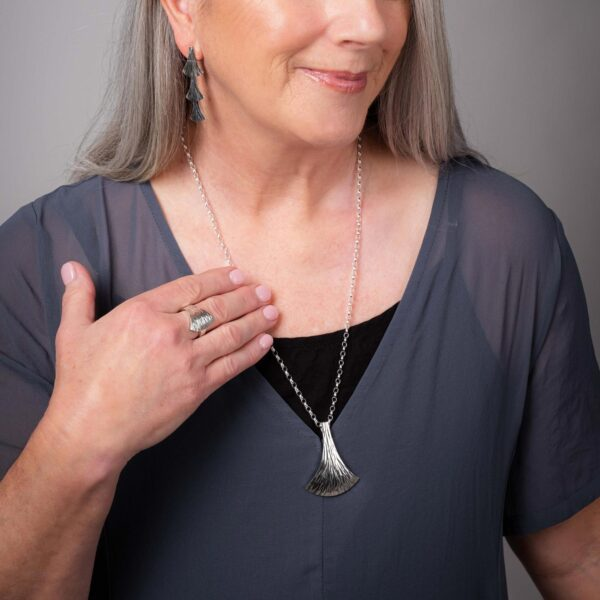 Model wearing the Emergence Silver Ring with the Large Silver Pendant and Cascade Earrings by Black Matter